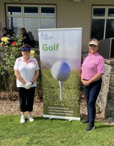 Picture of 2 ladies standing beside a NCBI Golf Banner